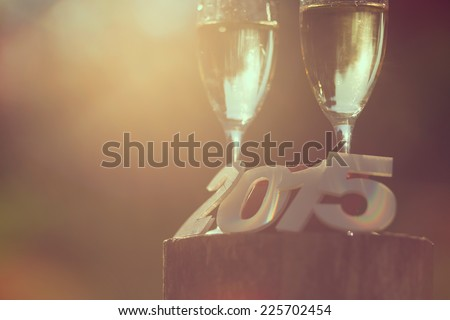 Champagne glasses with cardboard numbers 2015 and lens flare effect - stock photo