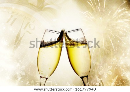 Champagne glasses with clock and fireworks - stock photo
