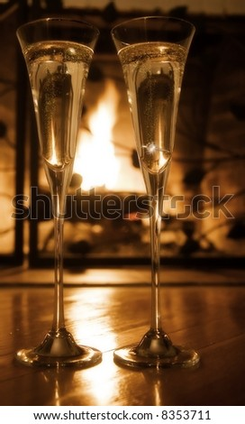 Champagne glasses with engagement ring in front of the fireplace.  Selective focus, gold tone - stock photo