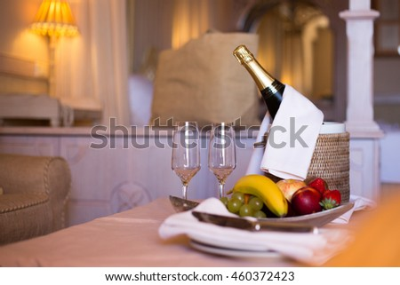 Champagne in a Hotel Room, Ice Bucket, Glasses and Fruits on a Plate - Honeymoon Concept
