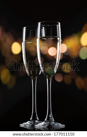 Champagne in glass on black background with color bokeh