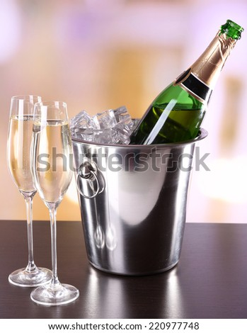 Champagne in glasses and bottle in restaurant - stock photo