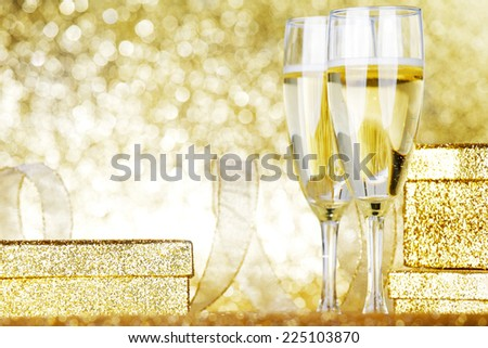 Champagne in glasses and gift box on golden background with twinkle lights - stock photo
