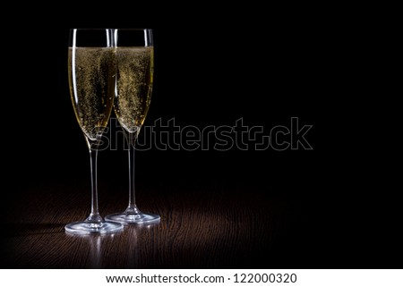 Champagne into glass on a black and wooden table - stock photo