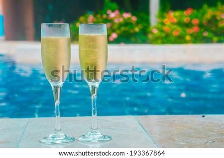 Champagne near swimming pool - stock photo