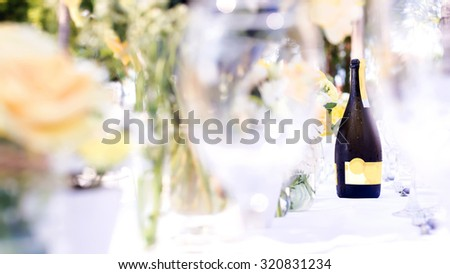 champagne on elegance table set up white, green and yellow flowers theme, selective focus. - stock photo