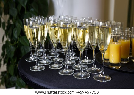 Champagne poured into glasses stands next to the orange juice on the table black cloth