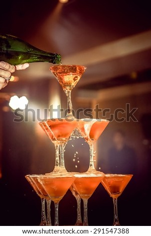 champagne poured over the champagne tower - stock photo