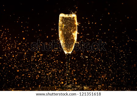 Champagne pouring in glass on a black background - stock photo