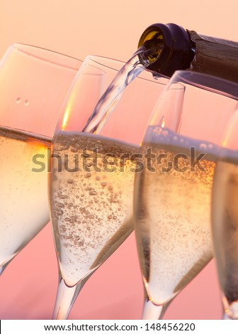 Champagne pouring into glasses with a sunset background - stock photo