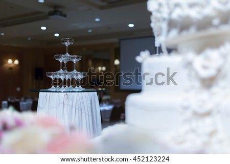 Champagne tower and wedding cake in front of. - stock photo