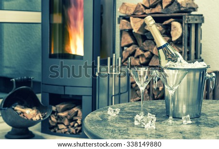 Champagne, two glasses and fireplace. Festive home interior. Romantic arrangement. Selective focus. Vintage style toned picture - stock photo