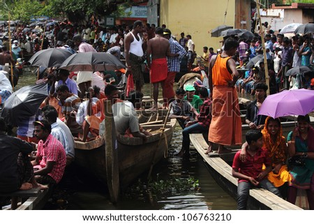 CHAMPAKKULAM, INDIA - JUL 03 : People in groups gathered to watch the Snake boat racing at the banks of Pumba river on July 03, 2012 at Champakkulam, Kerala, India. - stock photo