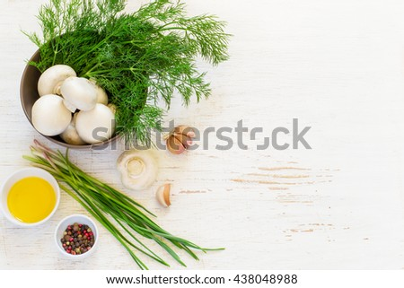 Champignon mushrooms and herbs in a bowl, top view, space for text - stock photo