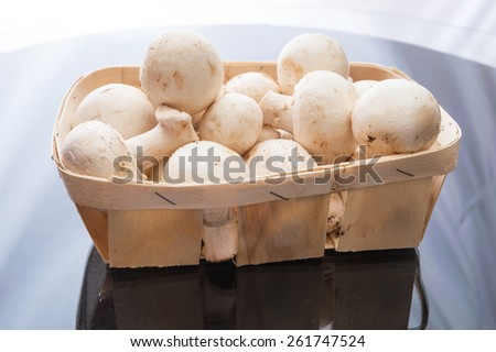 Champignon mushrooms in a basket on a glass table - stock photo