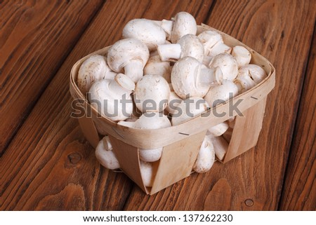Champignon mushrooms in a basket on a wooden table. close-up - stock photo