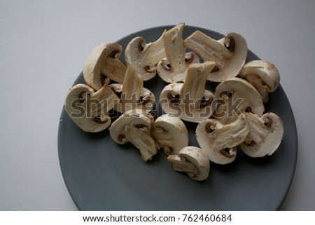 Champignon slices isolated on a side of grey concrete plate