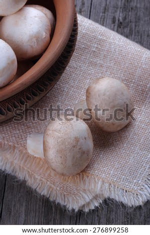 Champignons in a ceramic plate on old wood table - stock photo