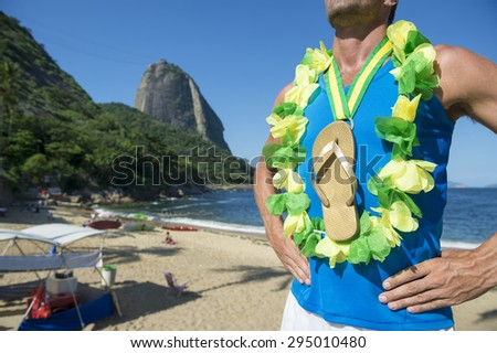 Champion athlete wearing Brazil colors lei around his gold medal flip flop celebrating at Red Beach Rio de Janeiro Brazil  - stock photo