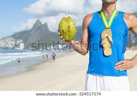 Champion athlete with a gold medal flip flop celebrating with coco gelado green coconut on Ipanema Beach Rio de Janeiro Brazil  - stock photo