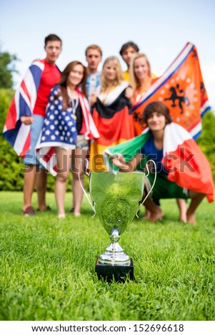 Championship trophy on grass with athletes of various nations in the background - stock photo
