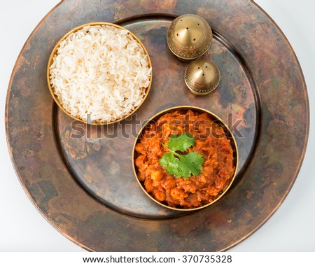 Chana masala on a rustic copper plate photographed from overhead. - stock photo
