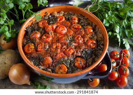 Chanakhi - traditional Georgian dish of lamb stew with tomatoes, aubergines, potatoes, greens, onion and garlic in clay pot on the wood table. Georgian cuisine. horizontal - stock photo
