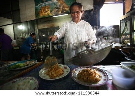 CHANG, THAILAND - JANUARY 23:  Unknown vendors prepare food at a street side restaurant on Jan 23, 2012 in Chang, Thai. Government figures indicate more 16,000 registered street vendors in Thailand. - stock photo