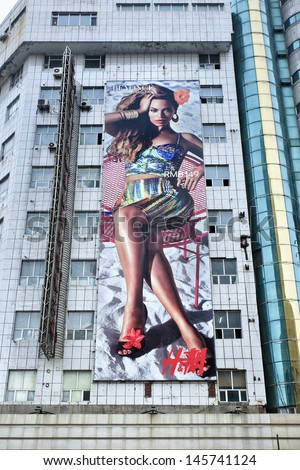 """CHANGCHUN-CHINA-JULY 8. H&M billboard with Beyonce on a flat. The American multitalented pop star shines in the """"Beyonce as Mrs. Carter in H&M""""?� campaign for summer 2013. Changchun, July 8, 2013. - stock photo"""