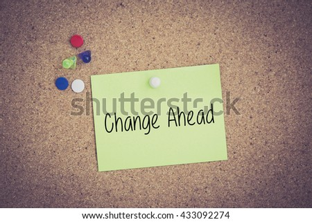 Change Ahead written on sticky note pinned on pinboard - stock photo