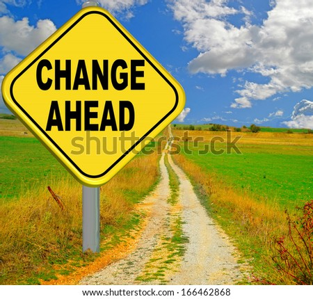 change ahead yellow sign - urban street background - green meadows blue sky and clouds - stock photo