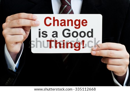 Change is a Good Thing! Businessman holding a card with a message text written on it - stock photo
