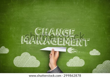 Change management concept on green blackboard with businessman hand holding paper plane - stock photo