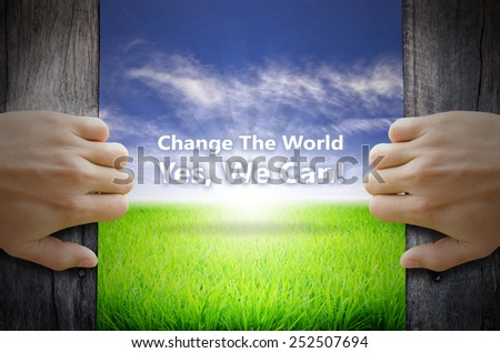 Change the world Yes we can motivational quotes. Hand opening an old wooden door and found a texts floating over green field and bright blue Sky Sunrise. - stock photo