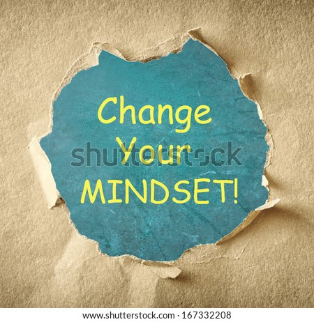 Change your mindset - motivational phrase written on board through torn paper hole  - stock photo