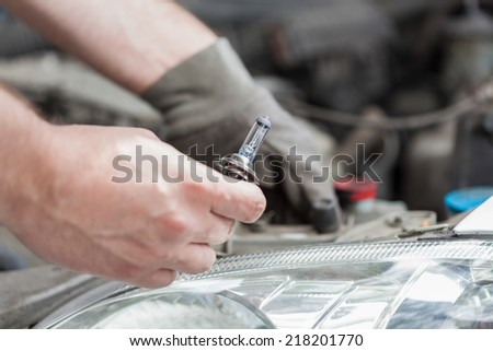 Changing a bulb in a car, horizontal - stock photo