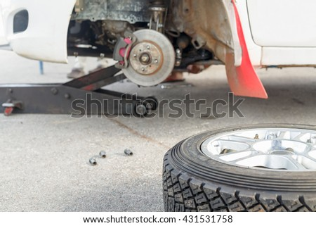 Changing a tire on a rally car in maintenance area - stock photo