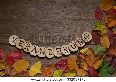 changing colorful leaves on wooden planks and pieces of wood with the letters spelling the german word for change burnt in them - stock photo