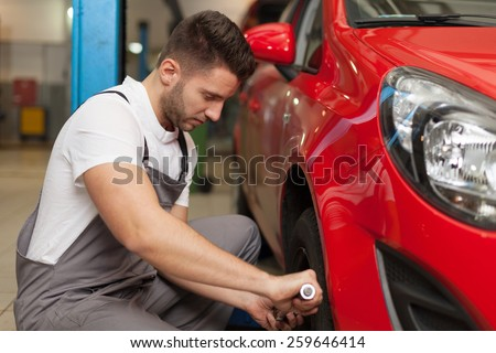 Changing the wheel. Focused mechanic using a torque wrench - stock photo