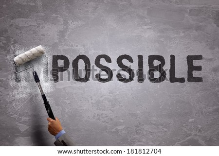 Changing the word impossible to possible by painting over and erasing part of the word with a paint roller on a concrete wall - stock photo