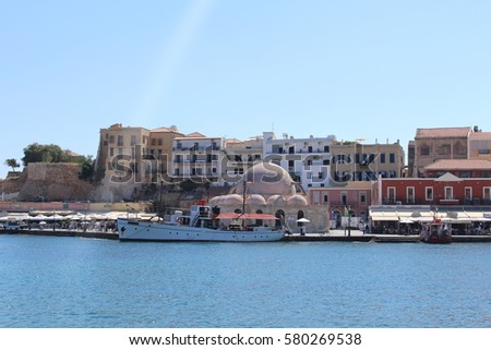 CHANIA, CRETE ISLAND, GREECE - JULY 26, 2016: A view of Kucuk Hasan Pasha Mosque and old Venetian Harbor promenade full of tourists and beautiful historical buildings at Akti Tompazi street.