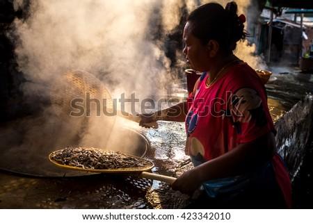 chanthaburi 15th May 2016 : unidentified asian woman boil small sea fish  - stock photo
