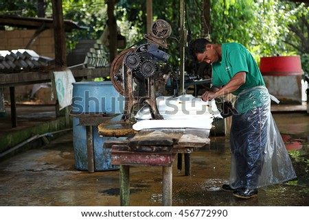 CHANTHABURI, THAILAND - NOV 24: Unidentified man farmer working machine rubber sheet in the small rubber factory in autumn on November 24, 2011 in Chanthaburi, Thailand