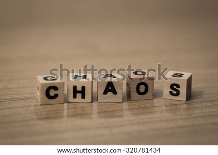 Chaos in messy order written in wooden cubes on a desk - stock photo
