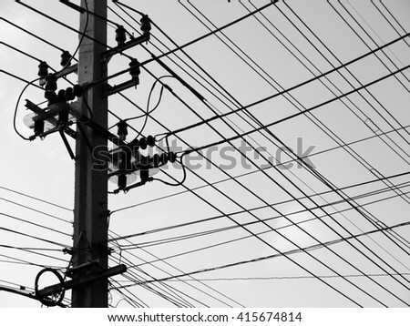 chaotic wire on pole with sky background in black and white