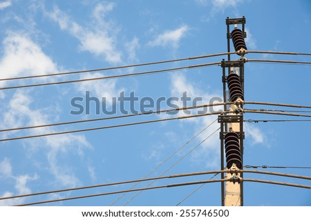 chaotic wire with nest on pole and blue sky background - stock photo