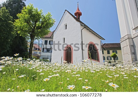 chapel with camomile field, Alps, Switzerland - stock photo