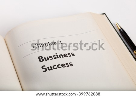chapter one,  in an open book with a pen,  business success, fake book