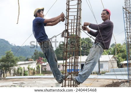 CHAPULTENANGO, CHIAPAS, MEXICO - DECEMBER 19, 2014: Two young men work diligently tying rebar together to prepare a column for pouring concrete in Chapultenango, Chiapas - stock photo