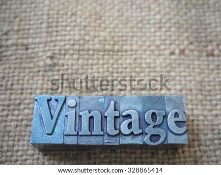"character ""VINTAGE"" from vintage iron letterpress block on sackcloth background - stock photo"